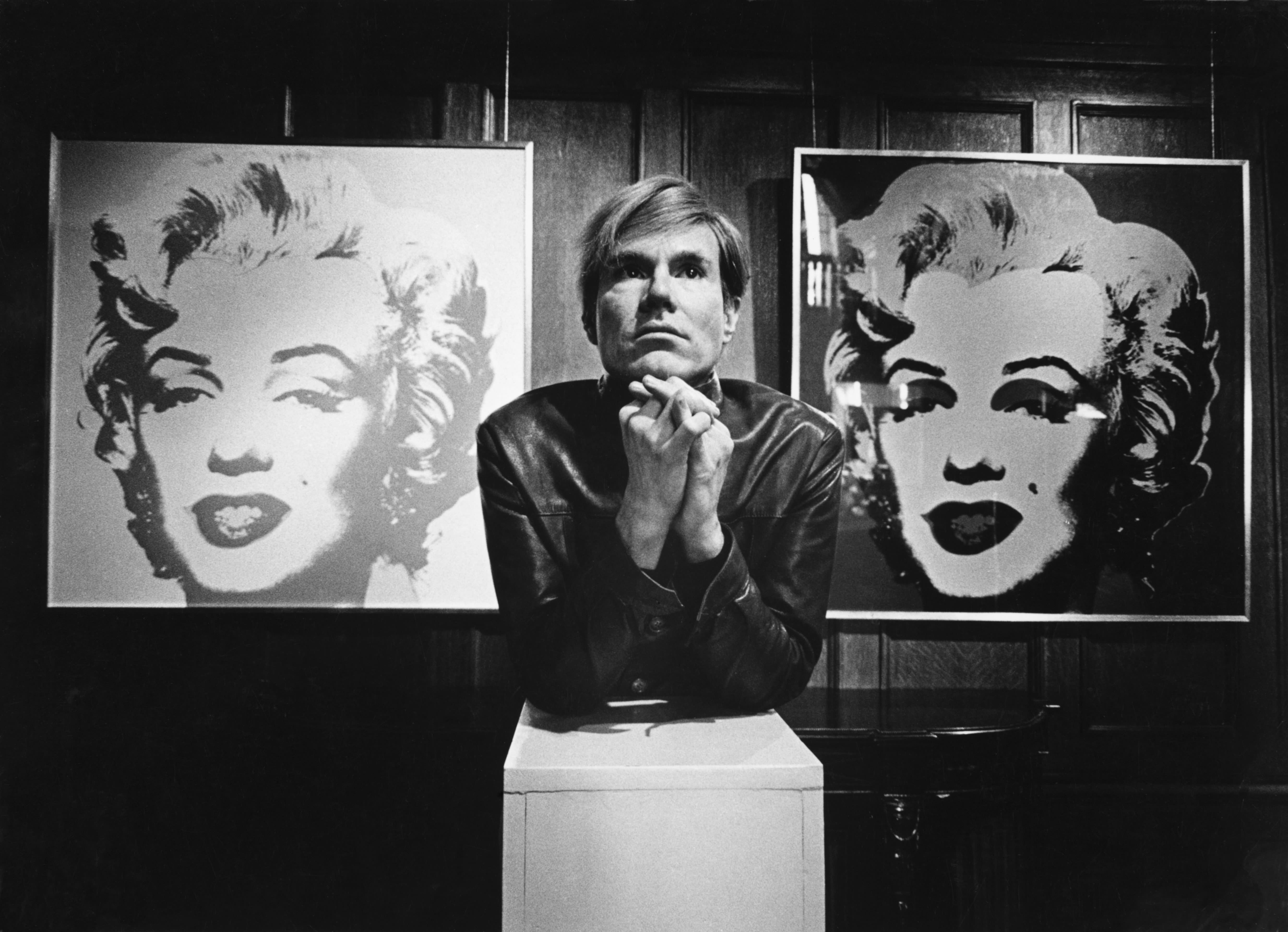Andy Warhol next to the image and screenprint of the 20 Marilyns painting
